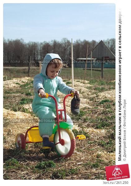 Маленький мальчик в голубом комбинезоне играет в сельском дворе с трехколесным велосипедом (5), фото № 261250, снято 20 апреля 2008 г. (c) Дмитрий Боков / Фотобанк Лори