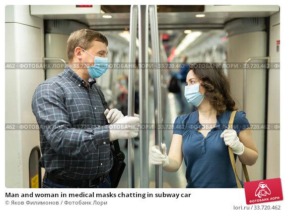 Man and woman in medical masks chatting in subway car. Стоковое фото, фотограф Яков Филимонов / Фотобанк Лори