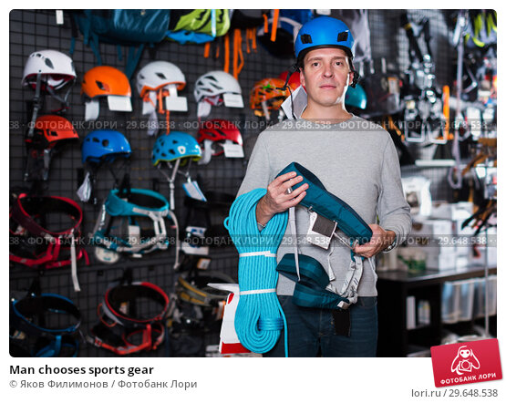 Купить «Man chooses sports gear», фото № 29648538, снято 25 октября 2017 г. (c) Яков Филимонов / Фотобанк Лори