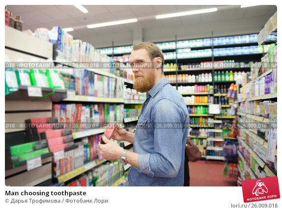 Купить «Man choosing toothpaste», фото № 26009018, снято 26 октября 2015 г. (c) Дарья Филимонова / Фотобанк Лори