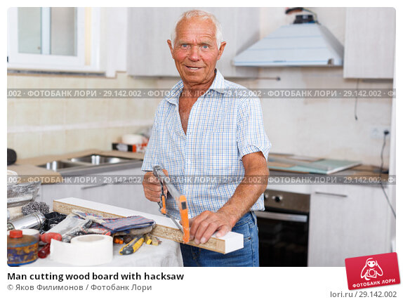 Купить «Man cutting wood board with hacksaw», фото № 29142002, снято 19 июня 2018 г. (c) Яков Филимонов / Фотобанк Лори