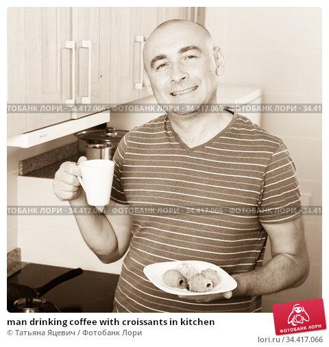 man drinking coffee with croissants in kitchen. Стоковое фото, фотограф Татьяна Яцевич / Фотобанк Лори