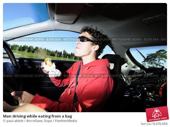 Купить «Man driving while eating from a bag», фото № 8676654, снято 13 июля 2020 г. (c) PantherMedia / Фотобанк Лори
