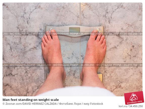 Man feet standing on weight scale. Стоковое фото, фотограф Zoonar.com/DAVID HERRAEZ CALZADA / easy Fotostock / Фотобанк Лори