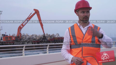 Купить «Man in a helmet, architect, engineer, manager tells about course of repair work of the coastline with a stone stock footage video», видеоролик № 28647710, снято 23 июня 2018 г. (c) Юлия Машкова / Фотобанк Лори