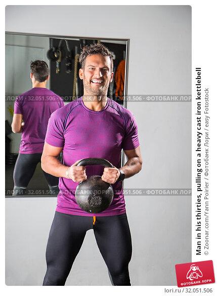 Man in his thirties, pulling on a heavy cast iron kettlebell. Стоковое фото, фотограф Zoonar.com/Yann Poirier / easy Fotostock / Фотобанк Лори