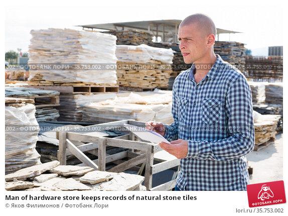 Man of hardware store keeps records of natural stone tiles. Стоковое фото, фотограф Яков Филимонов / Фотобанк Лори