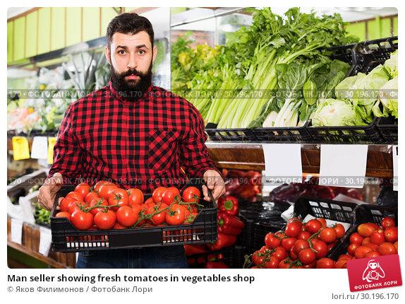 Купить «Man seller showing fresh tomatoes in vegetables shop», фото № 30196170, снято 15 ноября 2016 г. (c) Яков Филимонов / Фотобанк Лори