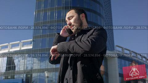 Купить «Man talking on the phone and looking on his watch outdoors», видеоролик № 28574894, снято 11 октября 2015 г. (c) Vasily Alexandrovich Gronskiy / Фотобанк Лори