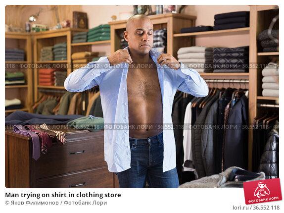 Man trying on shirt in clothing store. Стоковое фото, фотограф Яков Филимонов / Фотобанк Лори