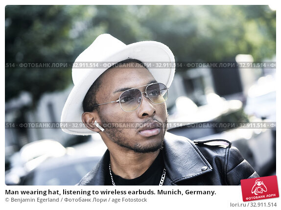 Man wearing hat, listening to wireless earbuds. Munich, Germany. Стоковое фото, фотограф Benjamin Egerland / age Fotostock / Фотобанк Лори