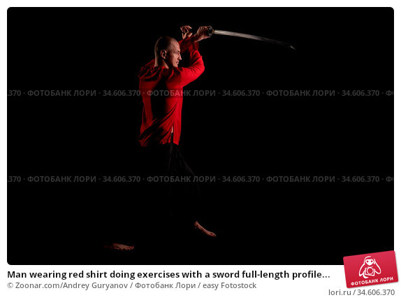 Man wearing red shirt doing exercises with a sword full-length profile... Стоковое фото, фотограф Zoonar.com/Andrey Guryanov / easy Fotostock / Фотобанк Лори