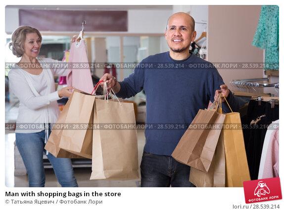 Купить «Man with shopping bags in the store», фото № 28539214, снято 22 февраля 2016 г. (c) Татьяна Яцевич / Фотобанк Лори