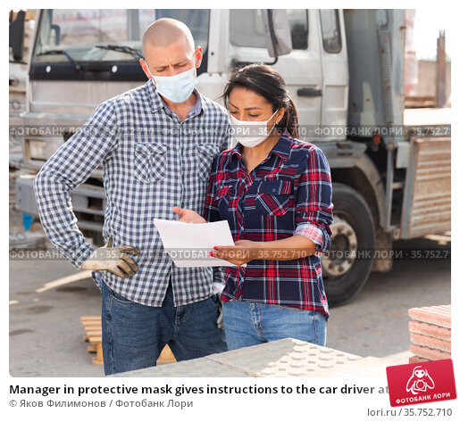Manager in protective mask gives instructions to the car driver at building materials storage site. Стоковое фото, фотограф Яков Филимонов / Фотобанк Лори
