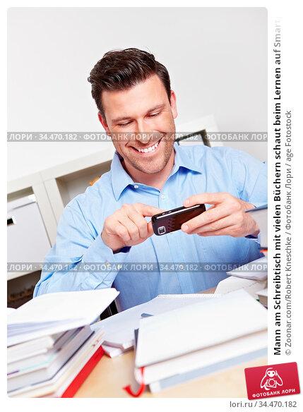 Mann am Schreibtisch mit vielen Büchern schaut beim Lernen auf Smartphone. Стоковое фото, фотограф Zoonar.com/Robert Kneschke / age Fotostock / Фотобанк Лори