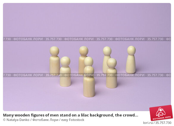 Many wooden figures of men stand on a lilac background, the crowd... Стоковое фото, фотограф Natalya Danko / easy Fotostock / Фотобанк Лори