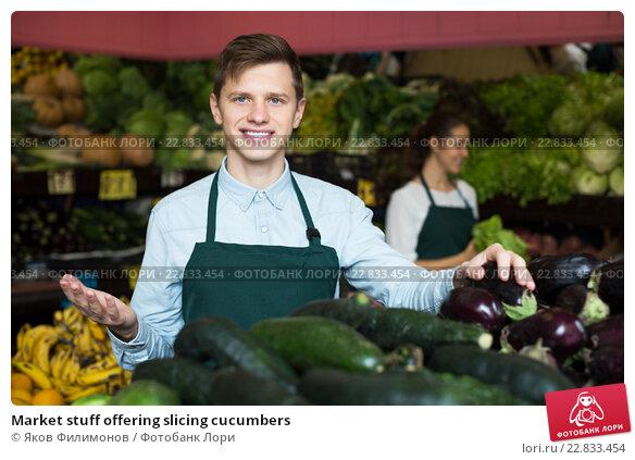 Купить «Market stuff offering slicing cucumbers», фото № 22833454, снято 19 апреля 2019 г. (c) Яков Филимонов / Фотобанк Лори