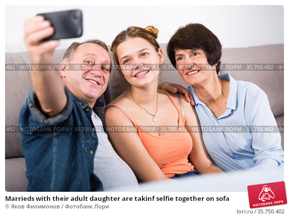 Marrieds with their adult daughter are takinf selfie together on sofa. Стоковое фото, фотограф Яков Филимонов / Фотобанк Лори