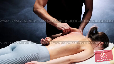 Massage session in dark studio - therapist massaging the woman's back with oil - massaging the shoulder blade. Стоковое видео, видеограф Константин Шишкин / Фотобанк Лори