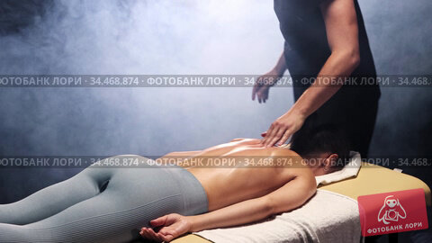 Massage session in the smoky studio - therapist massaging the woman's back while she is lying on a couch. Стоковое видео, видеограф Константин Шишкин / Фотобанк Лори