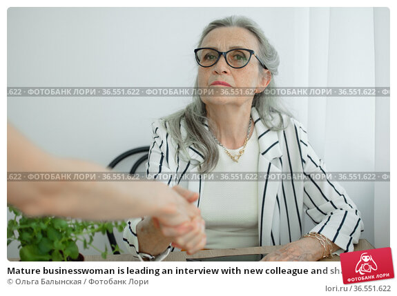 Mature businesswoman is leading an interview with new colleague and shaking their hand at the end. Business people concept. Стоковое фото, фотограф Ольга Балынская / Фотобанк Лори