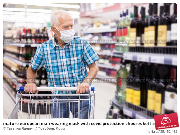 mature european man wearing mask with covid protection chooses bottle of alcohol in supermarket. Стоковое фото, фотограф Татьяна Яцевич / Фотобанк Лори