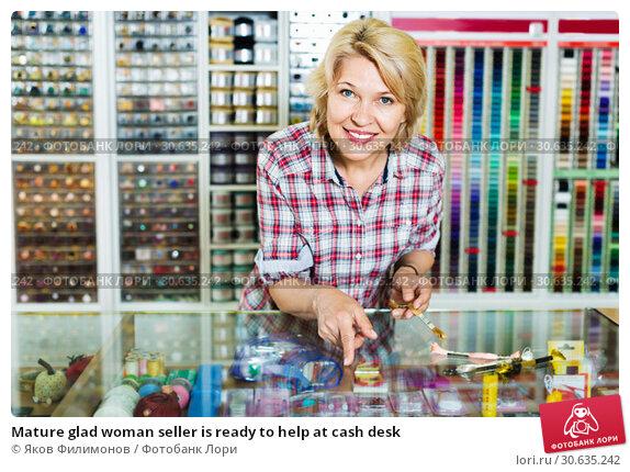 Купить «Mature glad woman seller is ready to help at cash desk», фото № 30635242, снято 16 июля 2019 г. (c) Яков Филимонов / Фотобанк Лори