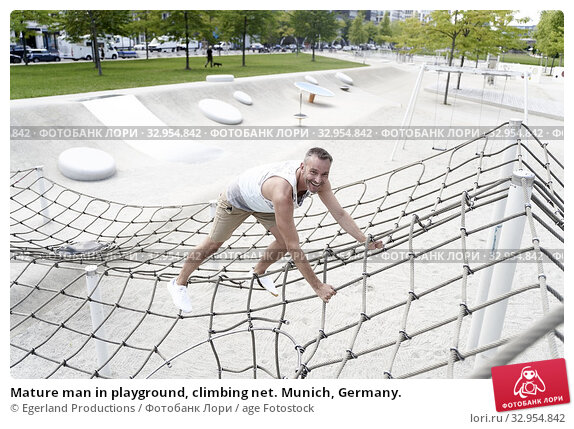Mature man in playground, climbing net. Munich, Germany. Стоковое фото, фотограф Egerland Productions / age Fotostock / Фотобанк Лори
