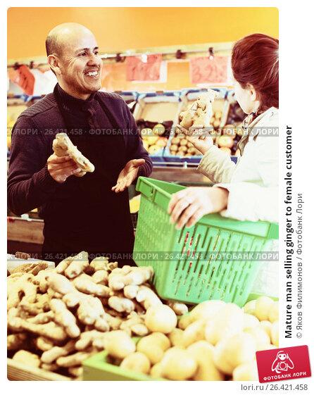 Купить «Mature man selling ginger to female customer», фото № 26421458, снято 19 февраля 2019 г. (c) Яков Филимонов / Фотобанк Лори