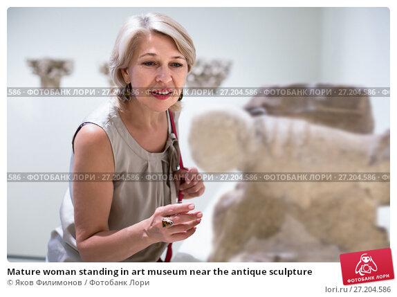 Купить «Mature woman standing in art museum near the antique sculpture», фото № 27204586, снято 7 октября 2017 г. (c) Яков Филимонов / Фотобанк Лори