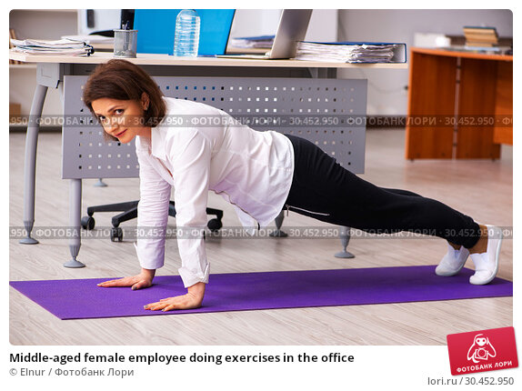 Middle-aged female employee doing exercises in the office. Стоковое фото, фотограф Elnur / Фотобанк Лори
