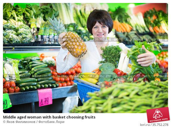 Middle aged woman with basket choosing fruits. Стоковое фото, фотограф Яков Филимонов / Фотобанк Лори