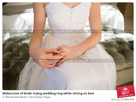 Midsection of bride trying wedding ring while sitting on bed, фото № 27069478, снято 2 мая 2017 г. (c) Wavebreak Media / Фотобанк Лори