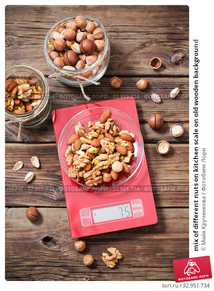 mix of different nuts on kitchen scale on old wooden background. Стоковое фото, фотограф Майя Крученкова / Фотобанк Лори