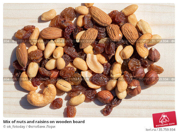 Mix of nuts and raisins on wooden board. Стоковое фото, фотограф ok_fotoday / Фотобанк Лори