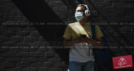 Mixed race man wearing face mask and using smartphone in the street. Стоковое видео, агентство Wavebreak Media / Фотобанк Лори