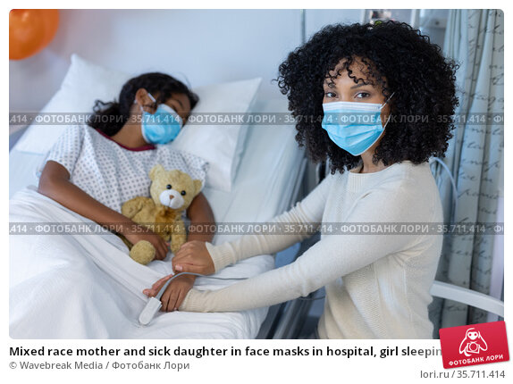 Mixed race mother and sick daughter in face masks in hospital, girl sleeping and holding teddy bear. Стоковое фото, агентство Wavebreak Media / Фотобанк Лори