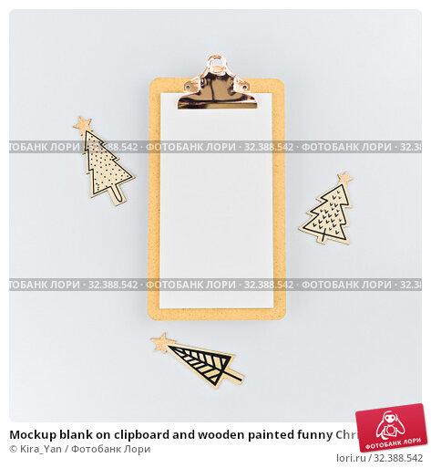 Купить «Mockup blank on clipboard and wooden painted funny Christmas trees on white», фото № 32388542, снято 14 декабря 2018 г. (c) Kira_Yan / Фотобанк Лори