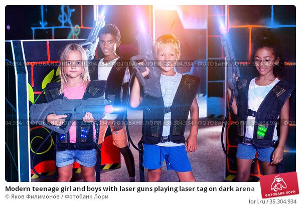 Modern teenage girl and boys with laser guns playing laser tag on dark arena. Стоковое фото, фотограф Яков Филимонов / Фотобанк Лори