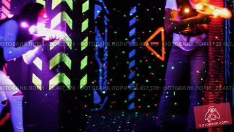 Купить «Modern young people with laser pistols playing laser tag on dark labyrinth», видеоролик № 28467378, снято 22 мая 2018 г. (c) Яков Филимонов / Фотобанк Лори