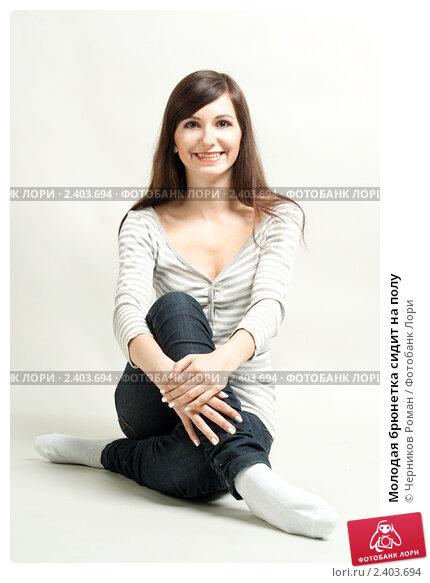 Купить «Молодая брюнетка сидит на полу», фото № 2403694, снято 19 февраля 2011 г. (c) Черников Роман / Фотобанк Лори