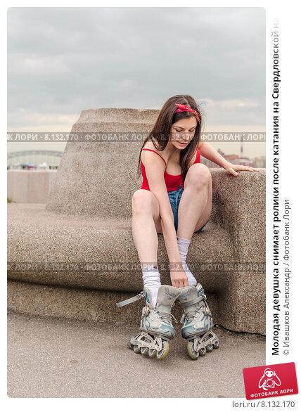 Молодая девушка снимает ролики после катания на Свердловской набережной. Санкт-Петербург. Стоковое фото, фотограф Ивашков Александр / Фотобанк Лори