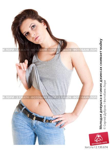 Купить «Молодая девушка в синих джинсах снимает майку», фото № 2130674, снято 30 октября 2010 г. (c) Сергей Дубров / Фотобанк Лори