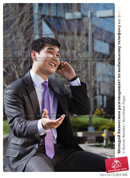 Молодой бизнесмен разговаривает по мобильному телефону на фоне офисного здания, фото № 5203346, снято 19 октября 2017 г. (c) Roman Barelko / Фотобанк Лори