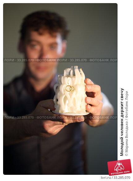Купить «Молодой человек держит свечу», фото № 33285070, снято 15 февраля 2020 г. (c) Марина Володько / Фотобанк Лори