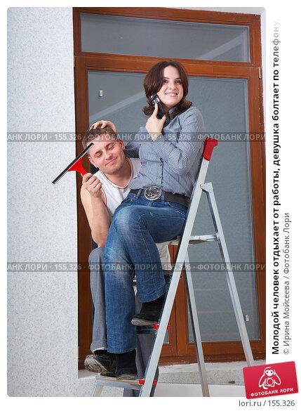 Молодой человек отдыхает от работы, девушка болтает по телефону, сидя на стремянке, фото № 155326, снято 5 декабря 2007 г. (c) Ирина Мойсеева / Фотобанк Лори