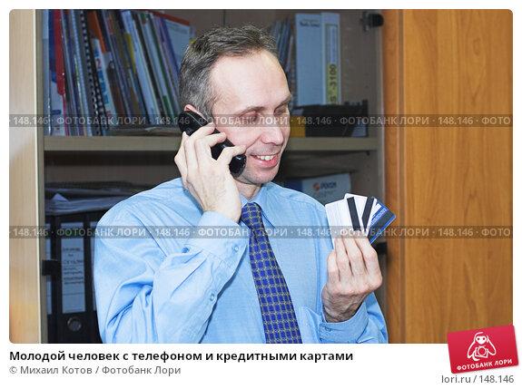 Купить «Молодой человек с телефоном и кредитными картами», фото № 148146, снято 26 апреля 2018 г. (c) Михаил Котов / Фотобанк Лори