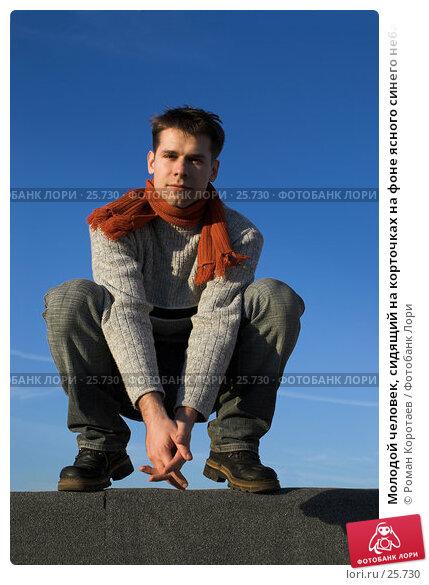 Молодой человек, сидящий на корточках на фоне ясного синего неба, фото № 25730, снято 20 марта 2007 г. (c) Роман Коротаев / Фотобанк Лори