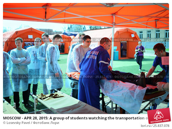 Купить «MOSCOW - APR 28, 2015: A group of students watching the transportation of the injured person during a training exercise at a field hospital on the Burevestnik stadium», фото № 25837078, снято 28 апреля 2015 г. (c) Losevsky Pavel / Фотобанк Лори