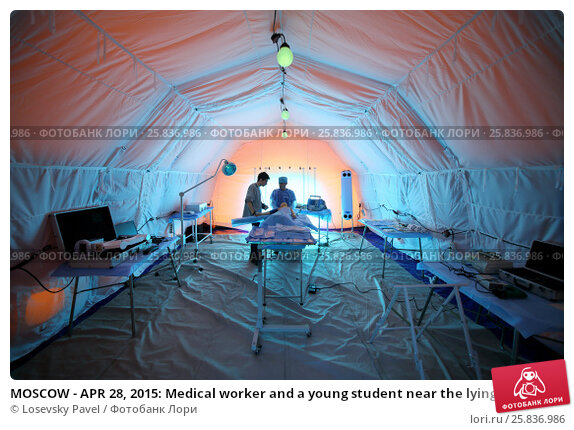 Купить «MOSCOW - APR 28, 2015: Medical worker and a young student near the lying dummy inside the tent in a field hospital», фото № 25836986, снято 28 апреля 2015 г. (c) Losevsky Pavel / Фотобанк Лори